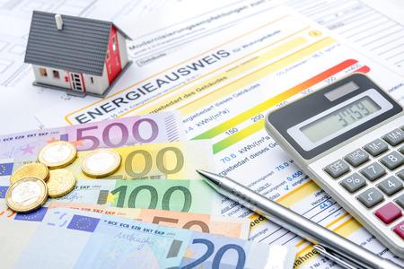 Casa con dinero, calculadora y un certificado de eficiencia energética Foto de archivo - 38005252