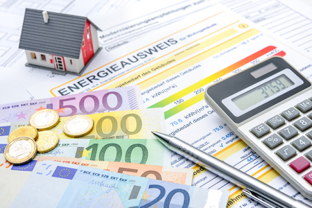 Huis met geld, rekenmachine en een energie-efficiëntie-certificaat Stockfoto