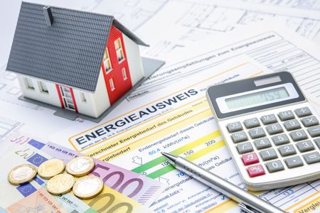cost reduction: House with money, calculator and an energy efficiency certificate Stock Photo