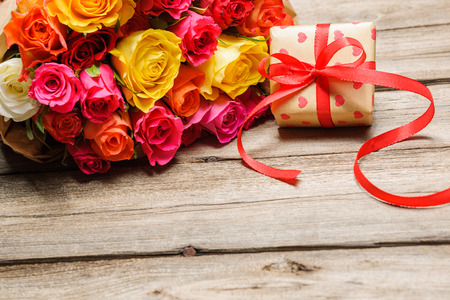 gift tag: Bunch of roses with a gift box on weathered wooden background