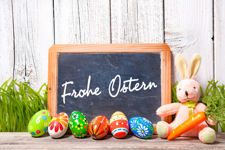 Background for Easter with german text. Easter decoration with sugar rabbit, eggs and message board photo