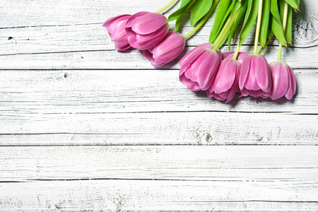 bouquet of spring pink tulips on wooden background photo