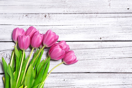 bouquet of spring pink tulips on wooden background