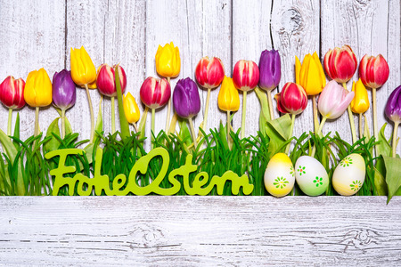 Spring tulips with Easter eggs and german text on wooden background. Background for Easter photo