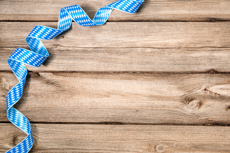 Bavarian ribbon on wooden background with copy space. Oktoberfest