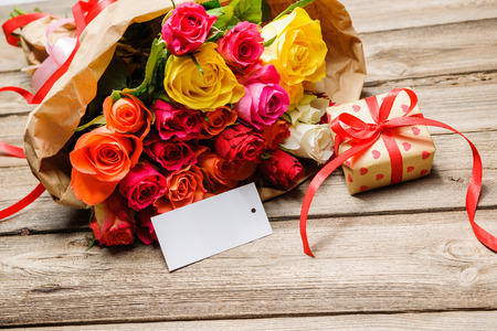 gift tag: Bunch of roses and gift box with an empty tag on wooden background Stock Photo
