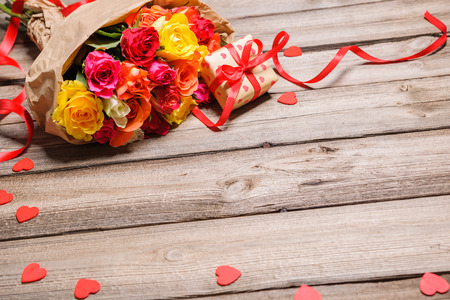 happy valentines day: Bunch of roses with a gift box on weathered wooden background
