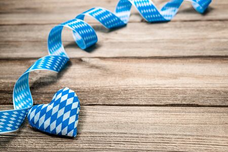 wiesn: Bavarian ribbon and a heart on wooden background with copy space