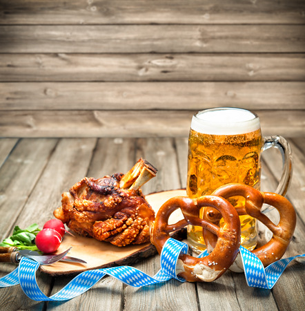 german culture: Roasted pork knuckle with pretzels and beer. Oktoberfest Stock Photo