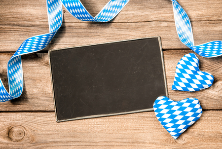 Background with empty board, Bavarian ribbon and hearts, Oktoberfest photo