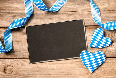 Background with empty board, Bavarian ribbon and hearts, Oktoberfest photo