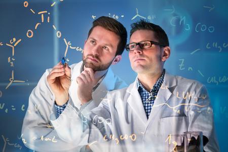 실험실에서 미디어 화면에서 작동하는 과학자의 그룹
