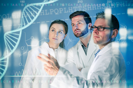 Groep genetici werken bij media scherm. Genetische manipulatie Stockfoto