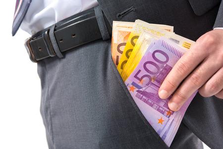billets euro: Un homme d'affaires dans un costume mettre de l'argent dans sa poche de pantalon Banque d'images