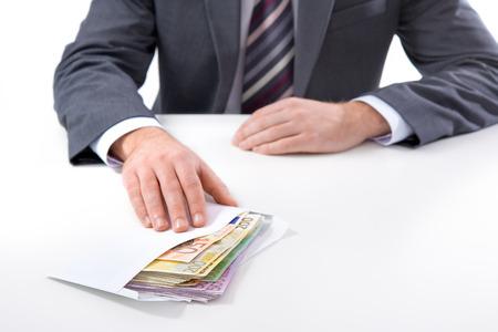 remuneraciones: Concepto - la corrupción. Hombre de negocios en un traje tiene un soborno