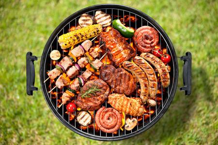 Diverse heerlijke gegrilde vlees met groenten over de kolen op een barbecue Stockfoto