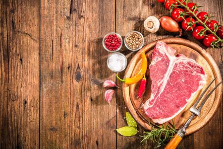 costilla: Filete sin procesar de la carne t-bone fresco y condimentos en el fondo de madera Foto de archivo