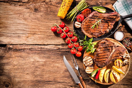 Beef steaks with grilled vegetables and seasoning on wooden background photo