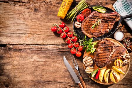 barbecue: Filetes de ternera con verduras a la parrilla y condimentos en el fondo de madera