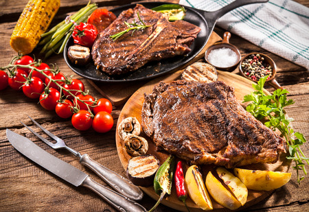 pan: Beef steaks with grilled vegetables and seasoning on wooden background