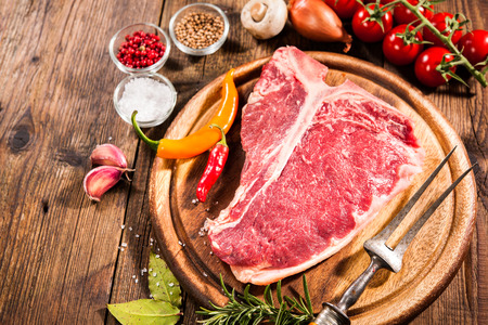 Raw fresh meat t-bone steak and seasoning on wooden background
