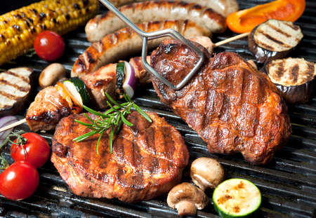 steaks: Assorted delicious grilled meat with vegetable over the coals on a barbecue