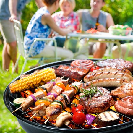 barbecue: Familia que tiene un partido de la barbacoa en su jard�n en verano Foto de archivo