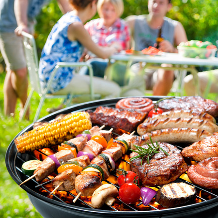 meat on grill: Family having a barbecue party in their garden in summer