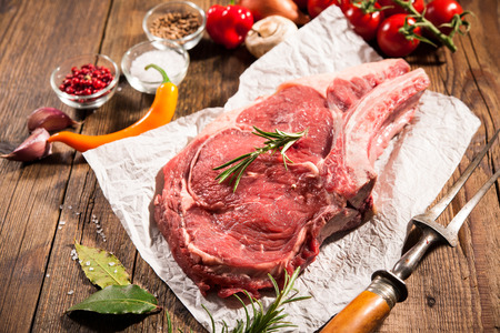 rib: Raw fresco filete de costilla de la carne y los condimentos en el fondo de madera Foto de archivo