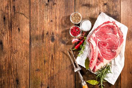 rib eye: Raw fresh meat rib eye steak and seasoning on wooden background