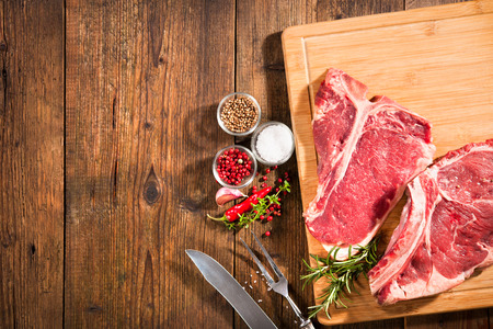 Raw fresh beef steaks and seasoning on wooden background Stock Photo