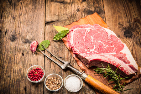 Raw fresh meat rib eye steak and seasoning on wooden background