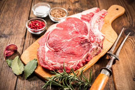 新鮮な生肉リブアイ ステーキと木製の背景に調味料