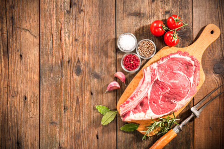 rib eye: Raw fresh meat rib eye steak and seasoning on wooden background