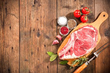 Raw frisches Fleisch Rib Eye Steak und Gewürze auf Holzuntergrund Standard-Bild - 40230731