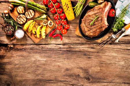 Beef steaks with grilled vegetables and seasoning on wooden background