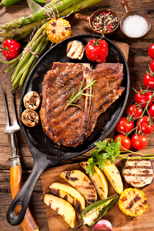 grilled potato: Beef steaks with grilled vegetables and seasoning on wooden background