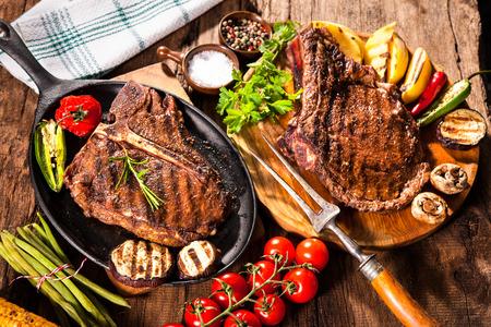 焼き野菜と木製の背景に調味料牛肉ステーキ