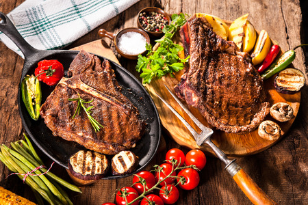 steak grill: Beef steaks with grilled vegetables and seasoning on wooden background