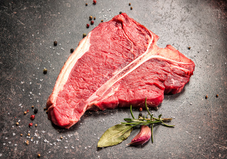 Raw fresh meat T-bone steak and seasoning on dark background 免版税图像