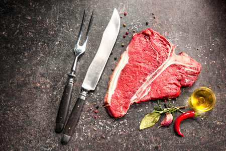 Raw fresh meat T-bone steak and seasoning on dark background Stock Photo