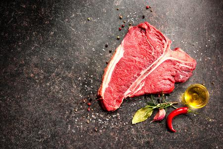 carne cruda: Filete de carne sin deshuesar fresca y el condimento en el fondo oscuro