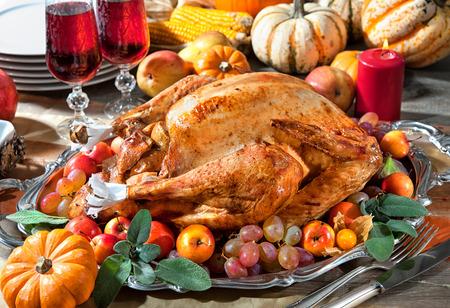 pavo: Cena de Acción de Gracias. Pavo asado en la mesa de fiesta con las calabazas, flores y vino