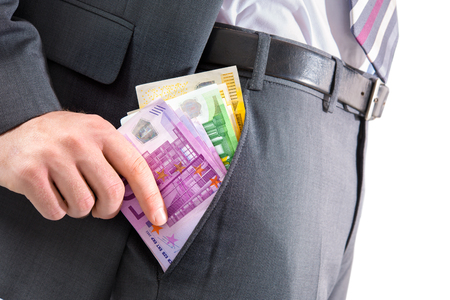venality: A businessman in a suit putting money in his pants pocket