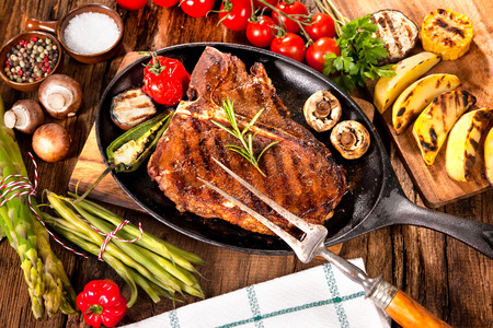 grilled vegetables: Beef steaks with grilled vegetables and seasoning on wooden background
