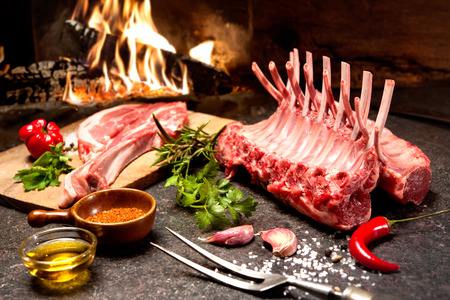 roast lamb: Rack of lamb with seasoning in front of a fireplace