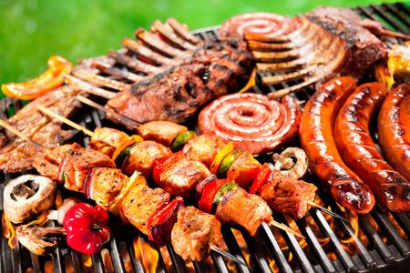 embutidos: Deliciosa carne a la parrilla con vegetales surtidos sobre las brasas de una barbacoa