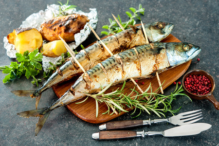 fish: Grilled mackerel fish with baked potatoes on stone background