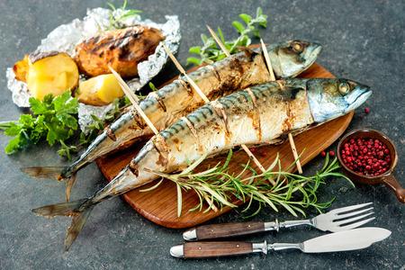 brochetas de frutas: Pescados de la caballa a la plancha con patatas cocidas al horno en el fondo de piedra