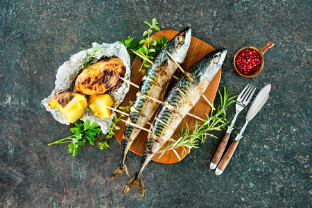 cooked fish: Grilled mackerel fish with baked potatoes on stone background